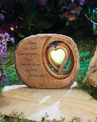 """Glow Heart Memorial Stone . $19.99. Hang it on a wall, too!. Glows in the dark (not solar). 8-1/4"""" x 6-1/4"""" x 1-1/2"""". Cold cast ceramic. Glow Heart Memorial Stone reads, """"I have not died, I am not gone...From heaven above my love shines on."""" The heart soaks up light during the day to shine at night. It has the look of carved stone with a glow-in-the-dark accent. Display it in the garden, or use the keyhole opening in the back for hanging on a wall. Can be used in..."""