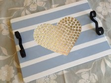 Handmade wooden tray with heart design mosaic inlay on a striped background