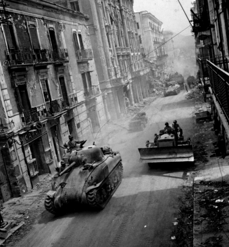 Fifth Army armor and heavy earth moving caterpillar proceeding through the damaged streets of Formia, Italy en route to Gaeta and Itri. 19 May 1944. (NARA, College Station).