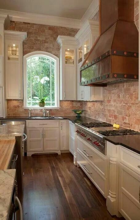 This kitchen..brick, tall white cabinets, professional grade appliances, arched window, hardwood floors...all of it