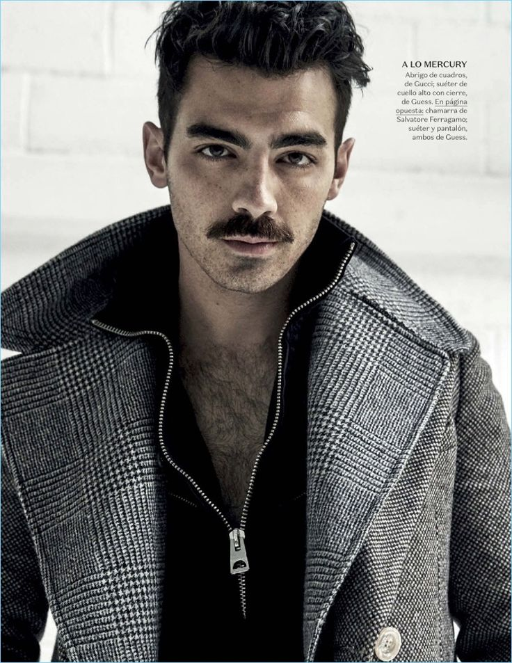 Rocking a mustache, Joe Jonas wears a Gucci coat with a Guess sweater.