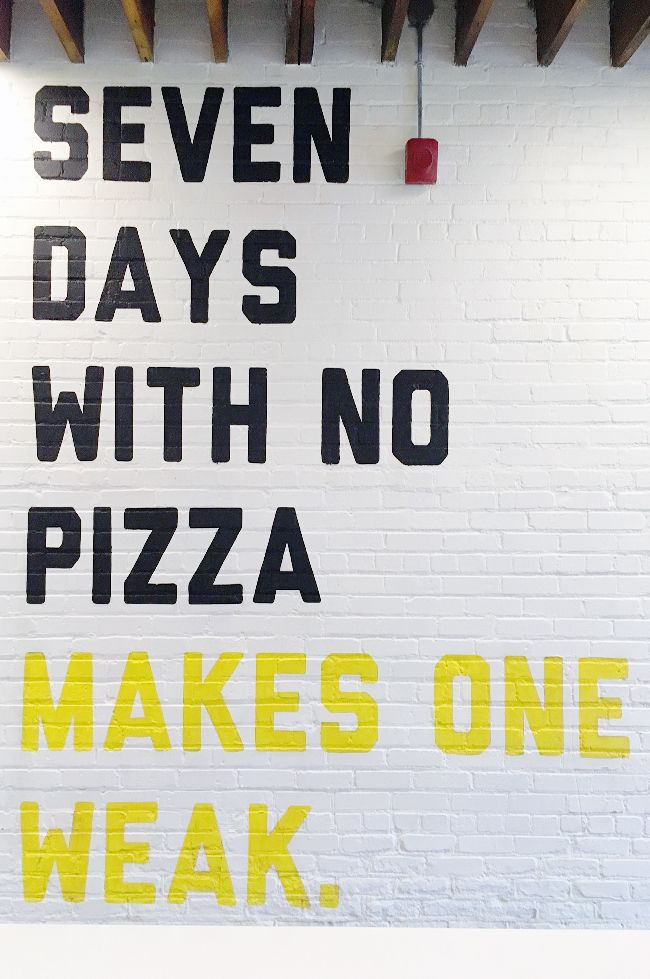 Black and white sign printed on brick wall in pizza restaurant, Cute!