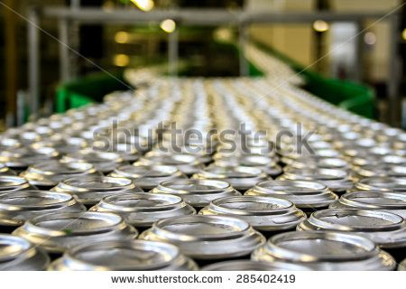 Lots of beverage cans on conveyor line at factory - stock photo