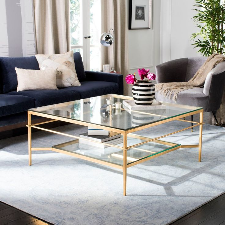 The luxurious Mieka gold leaf cocktail table is designed for elegant entertaining in transitional living rooms. Its see-through glass shelves give it the appearance of sculpture, while providing a practical, easy care surface for drinks and canapés. #CoffeeTable #Gold #Glass #Elegant #Safavieh