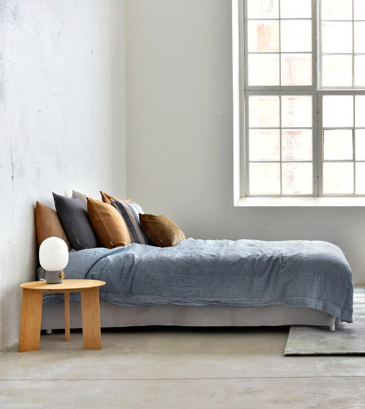 industrial loft apartment | bedroom goals | blue and brown is our favourite colour combination at the moment | white Bemz bedskirt | brown and acorn cushions | large industrial windows