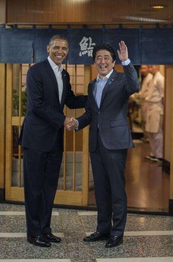 東京・銀座にあるすし店「すきやばし次郎(Sukiyabashi Jiro)」前で安倍晋三(Shinzo Abe)首相と握手をする米国のバラク・オバマ(Barack Obama)大統領(2014年4月23日撮影)。(c)AFP=時事/AFPBB News