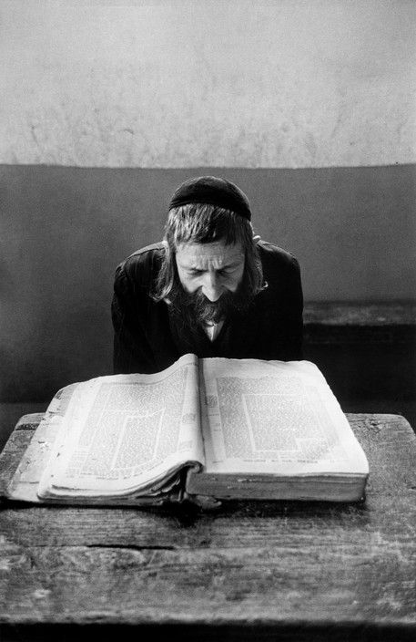 A teacher in a Yeshiva or orthodox learning academy in Jerusalem, reads aloud to childrem from the Talmud, source of Hebrew law and knowledge. Starting at the age of 4, boys study ten hours daily and are expected to memorise the Talmud's 63 tractates  (Robert Capa)