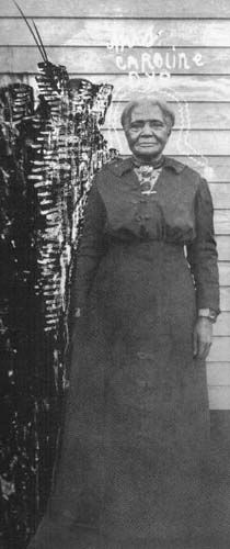 """Aunt Caroline Dye, born a Slave, c.1850-55, was a famous hoodoo woman or two-headed doctor who lived in Newport, Arkansas.  The crudely sketched aura around her head and the winged, dog-headed figure with its hand or paw on her right shoulder -- indicate that she maintained some form of contact with other-worldly spirits.  It is possible that the standing figure may represent a """"spirit guide"""" or the Devil's black dog one meets at the crossroads in an Afro-European ritual of empowerment."""