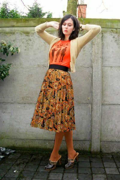 Cardigan, graphic tee, midi-length skirt, clogs.
