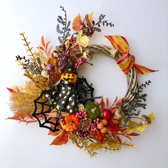 お部屋のインテリアやプレゼントにホウキに股がったパンプキンマンの可愛いハロウィンリースです。紅葉したリーフとかぼちゃが秋を感じさせてくれる大人可愛いリースです。感謝の気持ちを込めてプレゼント♡ ご結婚お祝い・お誕生日お祝い・ご新築ご開店お祝い・ハロウィンプレゼント・ハロウィンパーティ ♡リボン・カラーペーパー・セロファンでラッピングさせていただきます。花材:ドライフラワーのタタリカ・カラマツ・ぐいの実・松かさ・ソーラーフラワー・アーティフィシャルフラワーのベリー・ユーカリの実・枝・メイプルリーフ・フェルト蜘蛛の巣・リボン・フェイクりんご・カボチャ・ホウキなどsize:約33cm×30cm×7cm位「秋ハンドメイド2019」