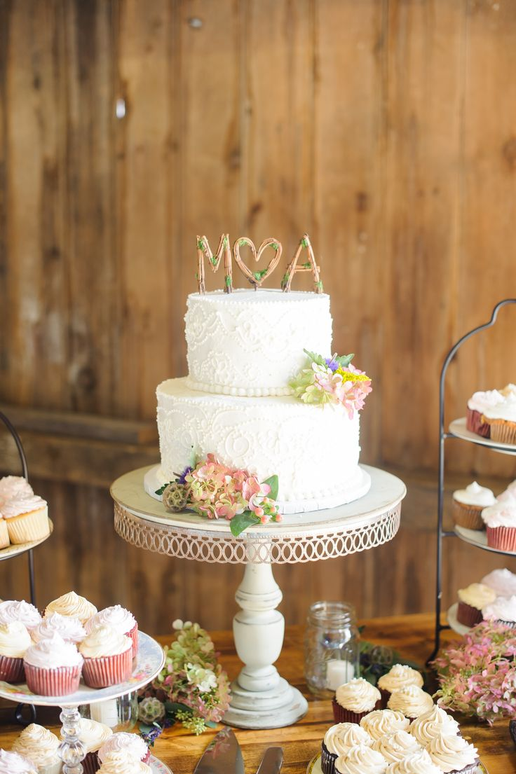 The two tier, white wedding cake was flavored blueberry with lemon filling and buttercream icing. The cake was decorated with lace piping and hydrangeas, scabiosa pods and hypercium. The Central Manor Bakery Creation stood on a vintage style cake stand.