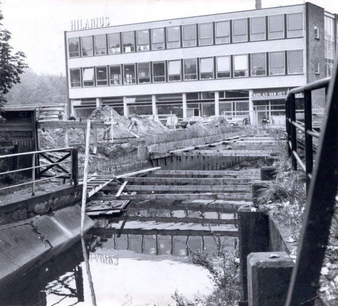 Bouw van schouwburg De Hagen, op de achtergrond Hilarius (Dagblad van het Oosten). Op de voorgrond het riviertje de Hagen | Mijn Stad Mijn Dorp