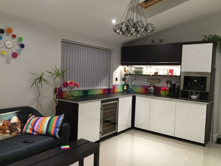 Breakfast area in extension adjacent to main kitchen. Multicoloured splashbacks with IKEA Ringhult high gloss white and Tingsryd black kitchen. Polished porcelain light grey floor tiles with Dulux Polished pebble Matt emulsion on walls.