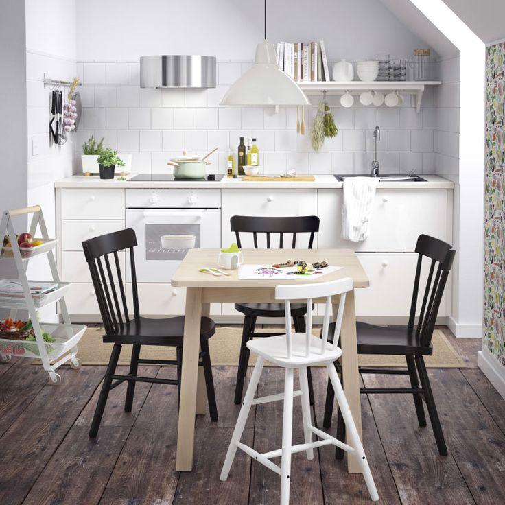 Cocina pequeña blanca con una mesita de comedor de abedul macizo pintado de blanco, sillas negras y una silla infantil blanca.