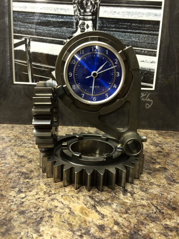 """Clock made from a ratio set, shift fork and dog ring. Parts could be from  current Dallara DW12 IndyCar used 2012-present, Dallara IR3 IndyCar Used  2003-2011 or various Sports Cars. Parts have serial numbers, ratio numbers  and model numbers to prove authentic. Used parts with new clock  workings.Clock is approximately 6"""" tall and weighs 4lbs.Clock runs on one  A76 button style battery.Available with 73mm blue faced clock insert."""