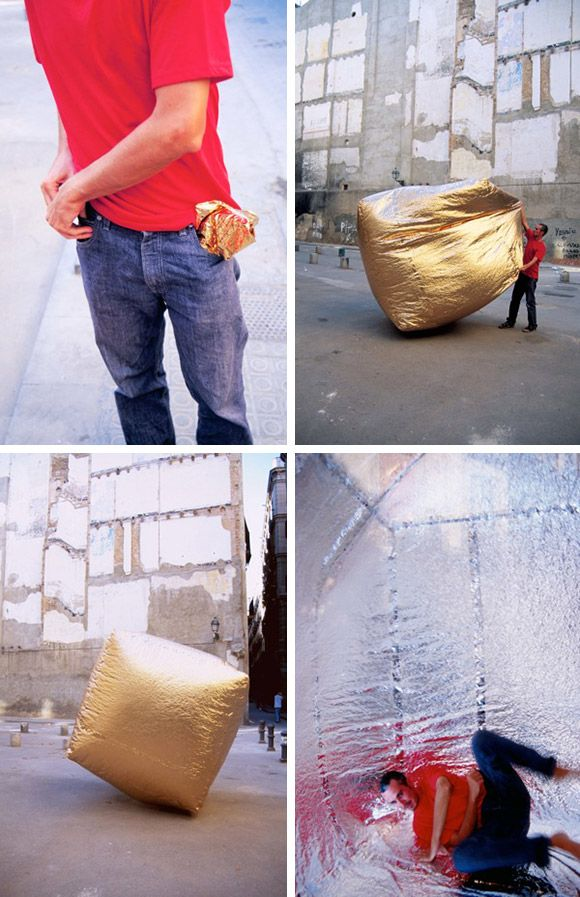 """""""The Basic House is a temporary housing solution so portable it can be folded up to fit in your pocket. Created from a metalized polyester material, when unfolded it self inflates with body heat or from the heat of the sun to provide an instant shelter. Once inside the shelter, the material reflects your body heat to keep the user warm. If reversed the material will reflect the sun to keep a cool interior."""""""