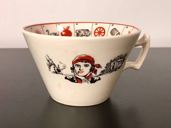 A fortune telling cup made in England in the 1920s, The Romany. Glazed ceramic with symbols inside the cup. Outside it features a gypsy on one side and on the other a read heart with the writing The Romany Fortune Telling Cup. These types of cups were made to divine fortunes from either tea leaves or coffee grounds (tasseography). During the Victorian age and until the Art Deco era, these games were very popular among the upper classes in Great Britain and in the United States: they were…