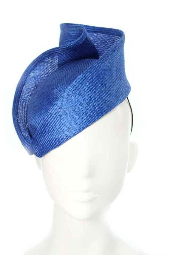 This is the perfect cobalt blue hat to wear with any number of outfits for special occasions or a day at the races! - Made with cobalt blueSisal . - Measuring approx. 19cm x 22cm (base) and 13cm at the heights point. - Held on the head with a brown elastic (should sit comfortably on most head sizes) - A piece of plastic comb is stitched to the back for extra security.  - This headpiece was lovingly arranged and constructed with the intention of wearing it on the right hand side of the head…