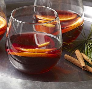 """""""Hot Glow Wine"""" - Gluhwein is a traditional hot beverage served in homes and sold on street corners during Christmas shopping season in the Bavarian state of Germany. The orange, lemon slices, and cinnamon sticks give the punch a sweet, fruity taste - the rum gives it an extra glow."""