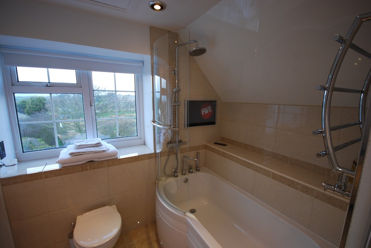 The bathroom TV was installed mid-level so that it can be watched either in the bath or when taking a shower. The curved towel rail is very handy.