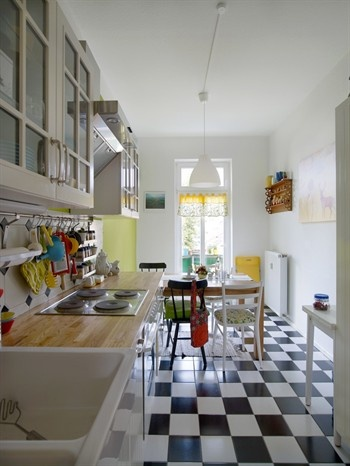 Kitchen with a sink and worktop, wall cabinets and chequered flooring
