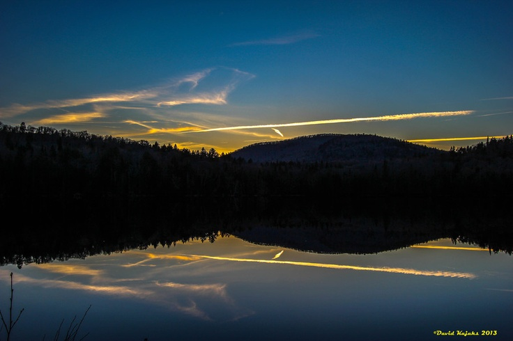 A mirroring reflection of the sunset on Lac Monroe in Quebec, Canada