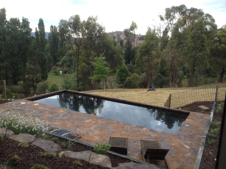 50x50mm Black mosaic pool tiles within a rural setting.