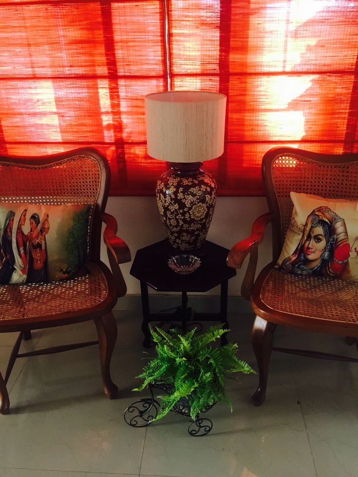 A cozy corner styled with traditional chairs, Bollywood-inspired throw pillows and vibrant red roman blinds