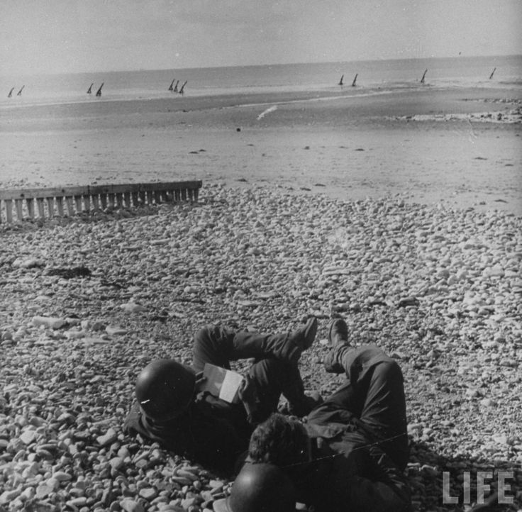 Pair of American soldiers (L-R, Peter Lazere & David Davies) resting & reading on a beach in Normandy following victorious AII Allied D-Day invasion. Location: Normandy, France Date taken:	June 1944