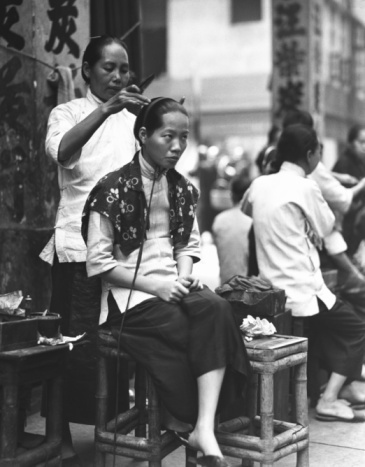 CHINA - CIRCA 1920s: Woman having her hair done by female hairdresser in sidewalk beauty parlour, Hong Kong.