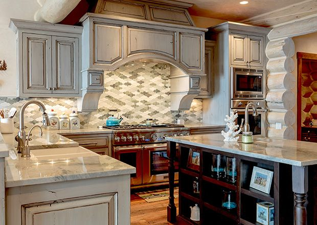 The neutral color palette extends to the gourmet kitchen, where grey-painted cabinets have a worn look.