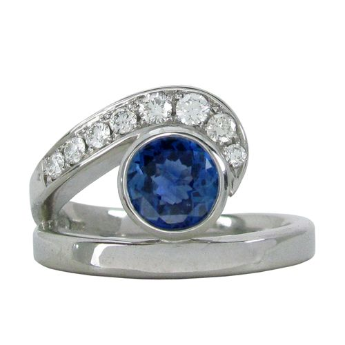 THE MOD SWIRL SAPPHIRE & DIAMOND RING  Set in a 14 karat white gold bezel is a 1.00CT round blue sapphire. A swirl of round brilliant diamonds hugs the bezel set sapphire and they range in size from 1.4mm-2.2mm with SI2 clarity. There is a total diamond carat weight of 0.25TCW. This sapphire and diamond ring is a size 7.25 tight which can also be sized. (R590)