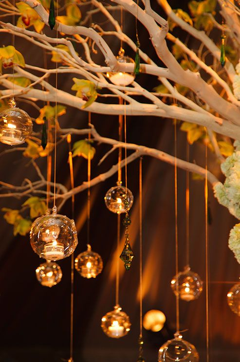 Glass bubble candle holders from CB2 make a huge statement alongside cymbidium orchids and hanging crystals.