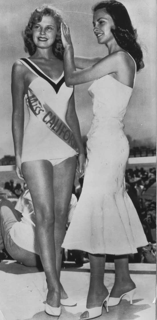 The explanation: Miss Modesto 1956 is securing the tiara hidden in the capacious hair of Miss California 1957. More beauty pageant photos from the Mercury News archives at the link.