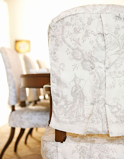 Tailored slipcovered dining chairs cotton toile in cream and taupe with covered buttons by Chris Barrett Design. Featured in Traditional Home.