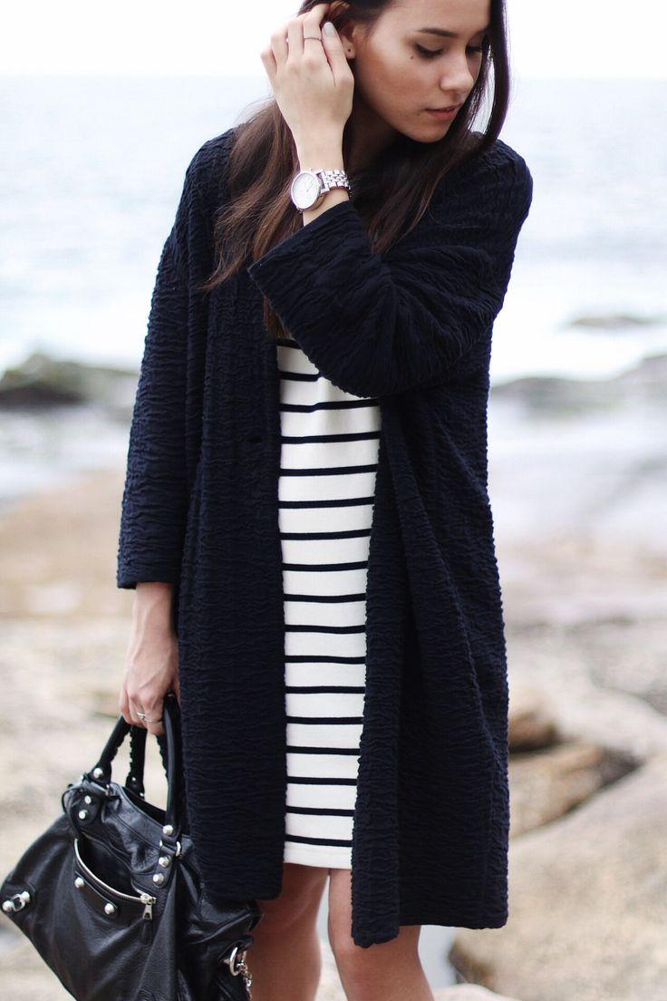 Nisi is wearing: Balenciaga Giant 12 City Bag, striped dress and an egg-shaped cardigan at Bondi Beach