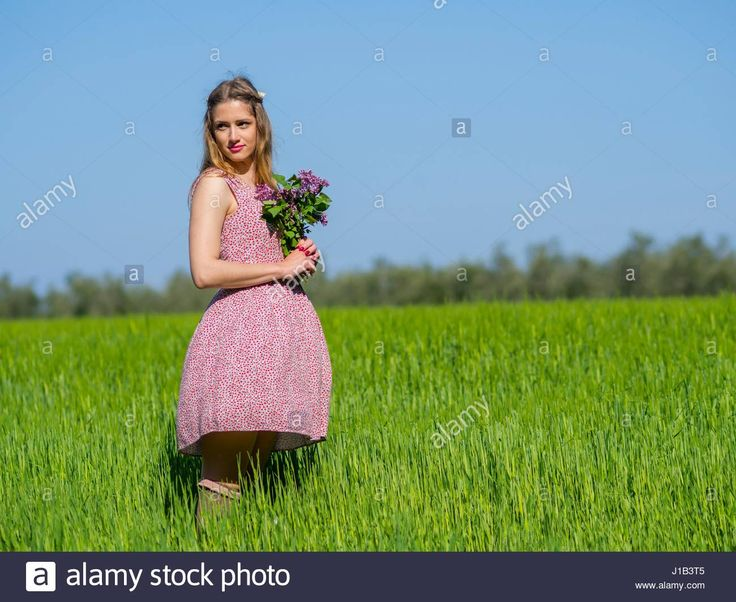 Download this stock image: Country-girl with flower flowers in hands serious looking back flying dress after wind blow, hold, holding carry carrying farm girl - J1B3T5 from Alamy's library of millions of high resolution stock photos, illustrations and vectors.