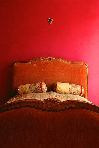 Saturated color, deep pinky red walls, rusty orange velvet antique bed head dressed with Indian pillow rolls. Charming bedroom bohemian eclectic.