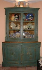 "Corner china cabinet made in Mexico.  On top of cabinet are three vases made by Capello of Guanajuato and purchased at his home in 3/2000.  See ""Artesanias de Guanajuato"" pages 22-27 for more information on Capello.  The inside top shelf  features work by Daphne Reynolds of Bierne, Texas.  Work is high fired and reminisent of early tourist pottery from Mexico. Middle shelf features pieces made by Gorky Gonzales of Guanajuato and purchased from him at his home 3/2000.  See  ""Great Masters of…"