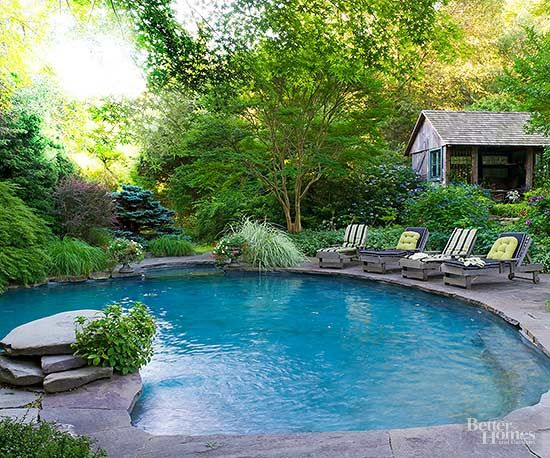 Peace reigns when a swimming pool nestles naturally into its setting. Thanks to mature plantings, an unconventional shape, and a rustic deck built from irregular blue stones, this pool looks and feels like a naturally occurring pond, albeit one that is conveniently served by a patio and a pool house./