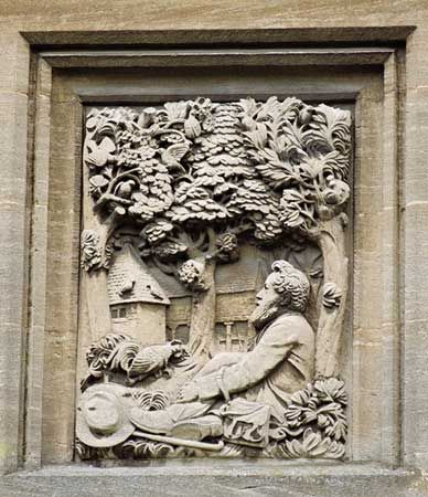Carved relief of William Morris by George Jack set on a wall to a design by Philip Webb for Cotswold Houses