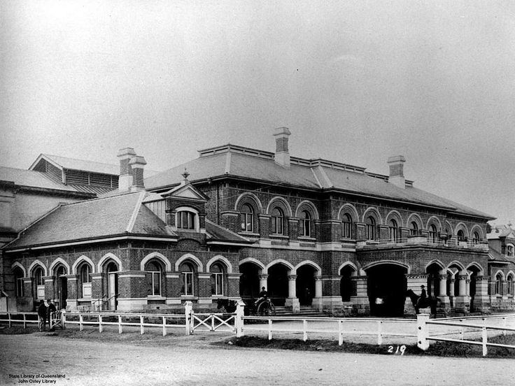 Roma Street Railway Station, Brisbane, Queensland, ca. 1888 - The main front entrance to the Roma Street Railway Station, is a large, attractive brick building with arched windows, multiple chimneys and a tiled roof. A man on a horse, and a person on a horse and cart can be seen in front of the entrance.