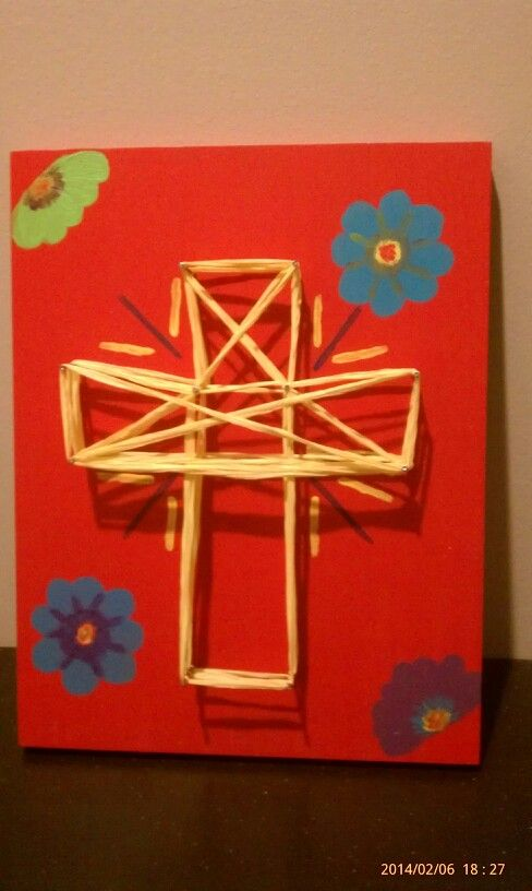 a cross made of wood, yarn,some nails  and  paint