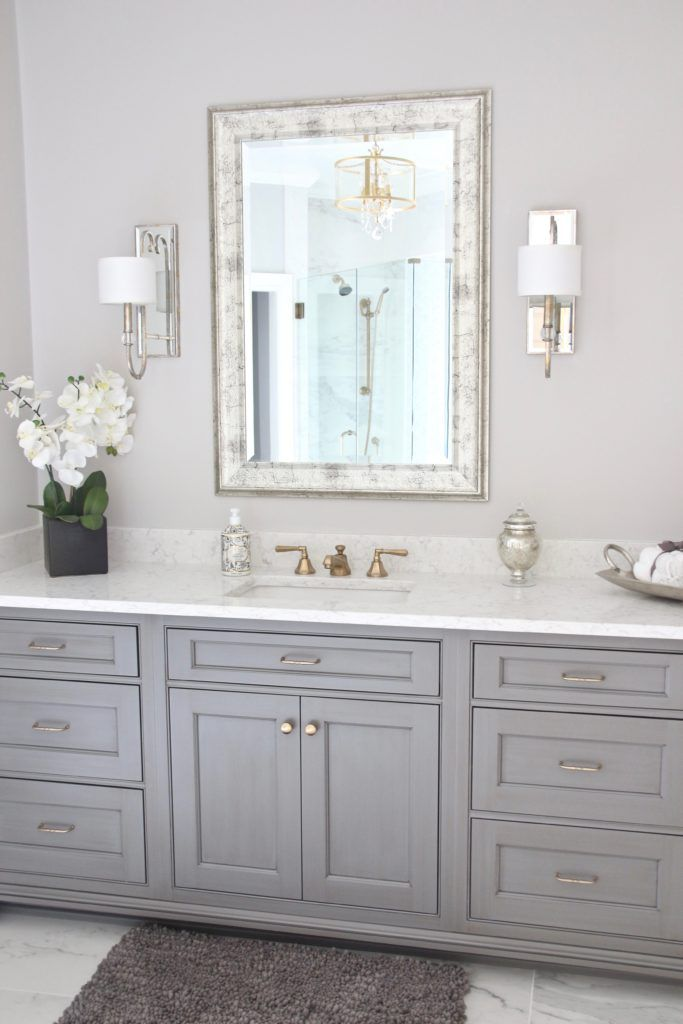 Gray And White Bathroom With Mirrored Accents And Gold Hardware