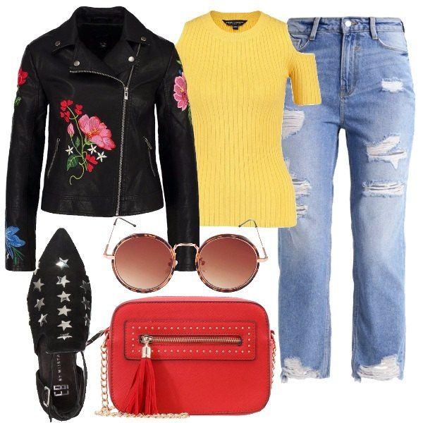 Giubbotto in ecopelle con applicazioni floreali, top giallo con cut out sulle spalle, jeans baggy destroyed, stivaletto con borchie a stella, tracolla rossa e occhiali tondi.