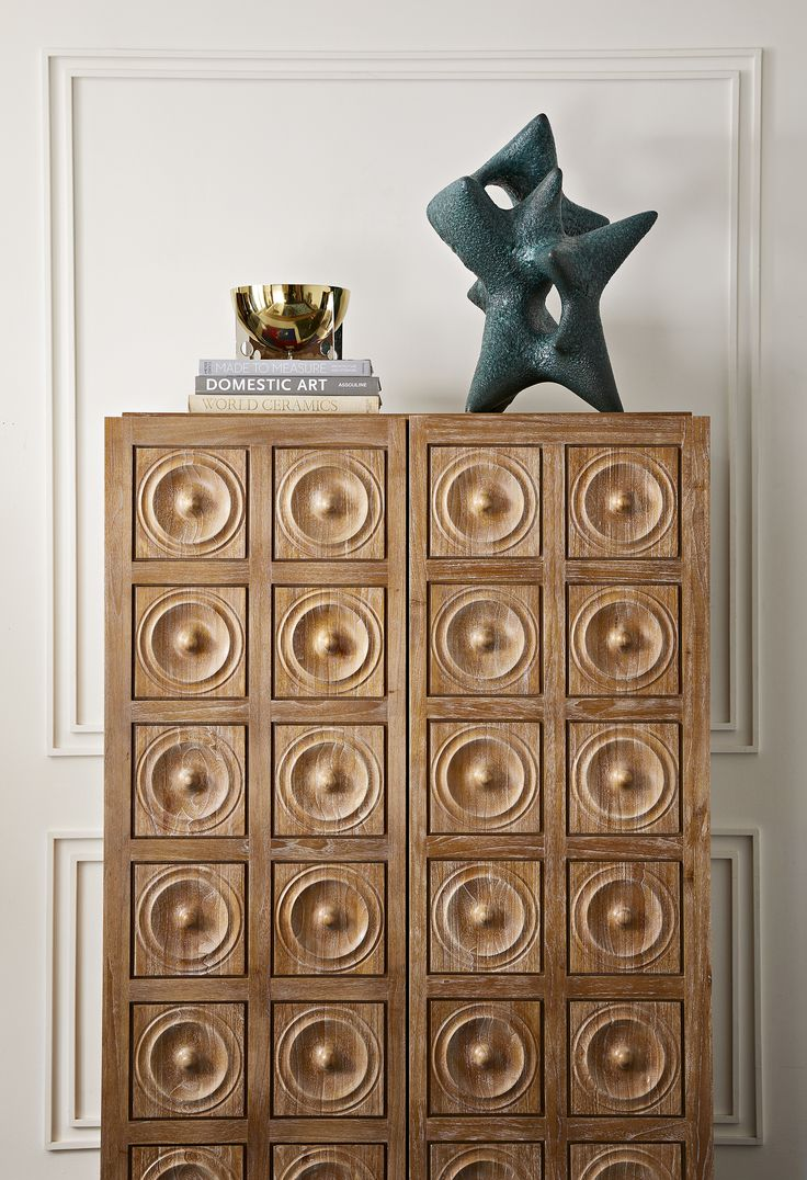 The Jonathan Adler Antwerp Cabinet our Antwerp Cabinet is the kind of furniture piece you fantasize about stumbling upon at a Paris flea market.   The futuristic yet inviting pattern of repeating wooden circles was inspired by tiles JA created for his Shelter Island House, which were in turn inspired by an Eva Hesse drawing.