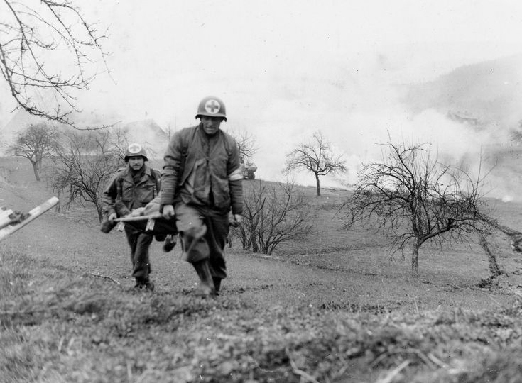 """"""" A pair of incredibly courageous medics dash through no-man's-land during a firefight outside Weschnitz, Germany on March 29, 1945. The photo was snapped as the medics carry a wounded cavalry trooper to safety while a tank creates a smoke screen to..."""