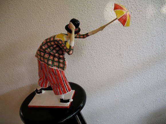 Escultura em papel de palhaço com sombrinha sob forte ventania. R$ 125,00