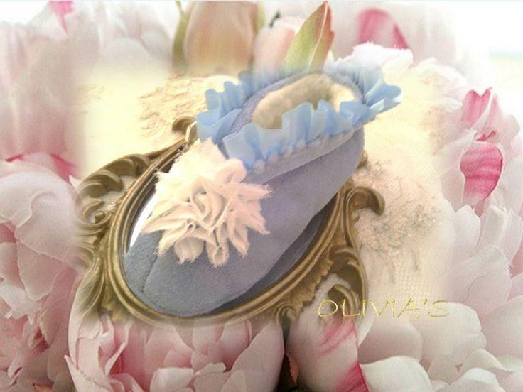 Babuchas celestes con flor blanca y volante con madroños celeste.