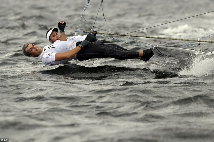 Italians Pietro Zucchetti and Ruggero Tita use the full length of their bodies to steer their boat in the 49er sailing event